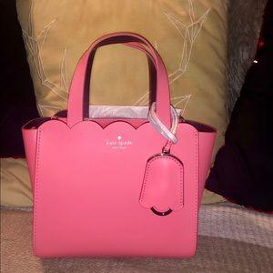 Pink Kate Spade mini bag with shoulder strap.